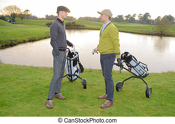 Male golfers chatting on the golf course