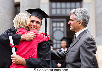 male graduate hugging his mother at graduation - happy male...