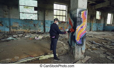 Male graffiti artist is decorating old damaged column inside empty industrial building with abstract pictures. Modern painter is using aerosol spray paint.