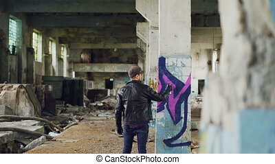 Male graffiti painter is creating abstract image with spray...