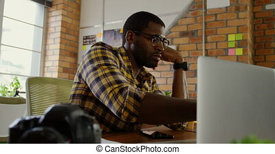 Male graphic designer working at desk in a modern office 4k