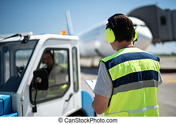 Male ground handling worker looking at partner sitting in the vehicle