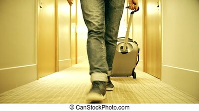 Male guest with suitcase goes along the hotel hallway - Man...