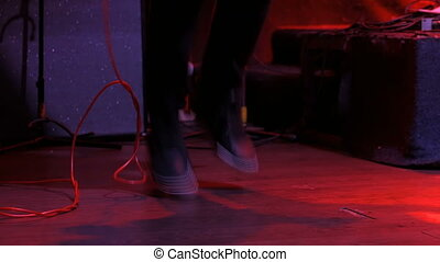 Male guitar player jumping and dancing on concert stage. Red...
