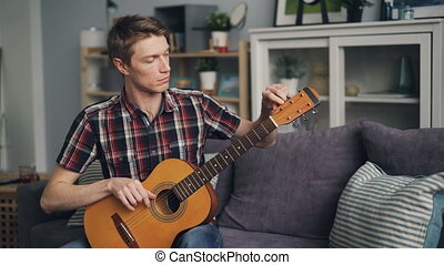 Male guitarist is tuning acoustic guitar checking sound...