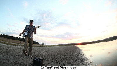 male guitarist street man musician playing the electric guitar at sunset by the water the sun sets