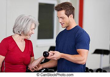 Male gym trainer instructing an elderly woman