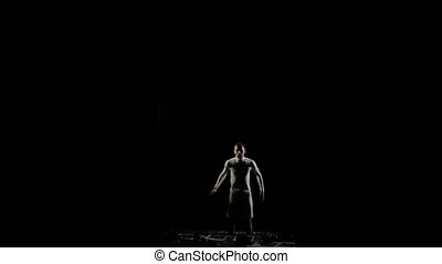 male gymnast on a black background in white clothes soars...