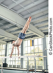 Male gymnast performing handstand on parallel bars