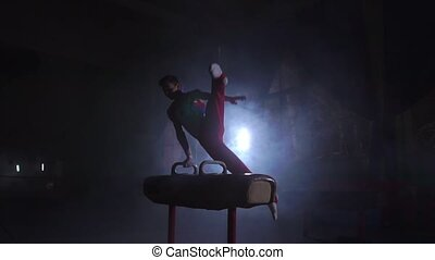 Male gymnast performs Pommel horse exercise in a dark room...
