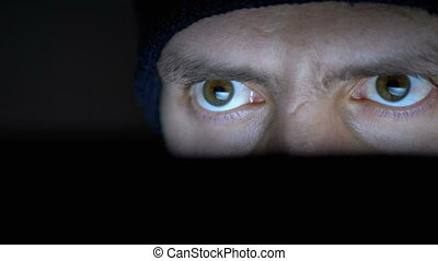 Male Hacker in Hat Working on Laptop Monitor at Night