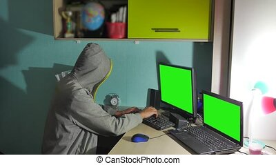 Male hacker indoor working on a computer. man hacker in hood...