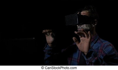Male hacker uses a virtual reality headset for his...