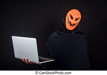 Male hacker with halloween mask carrying laptop