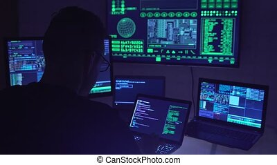 Male hacker working on a computer in a dark office room.