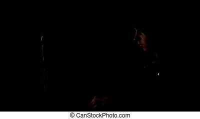 Male hacker working on a computer in a dark office room