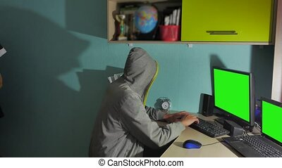 Male hacker working on a computer. man hacker in hood hiding...
