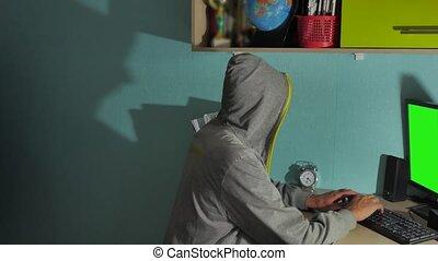 Male hacker working on a computer. man hacker in hood indoor...