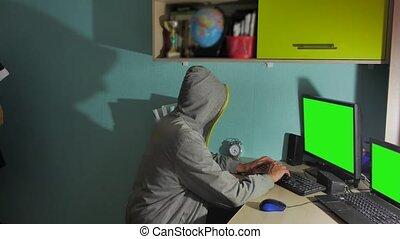 Male hacker working on a computer. man hacker in hood hiding...