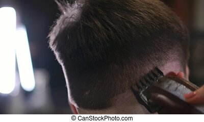 Male haircut with electric razor. Close up of hair trimmer...