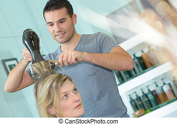 male hairdresser blow drying customers hair