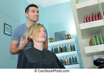 male hairdresser cutting female clients hair