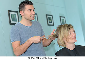 male hairdresser with female customer in a hair-salon