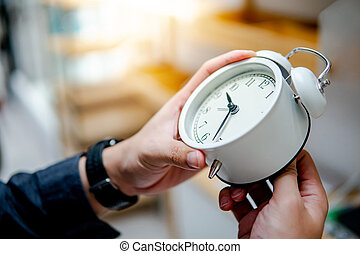 Male hand adjusting the time on white clock