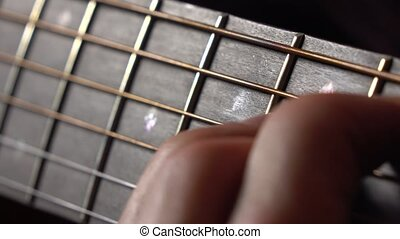 Male hand and strings on fretboard. Music performance. 4K...
