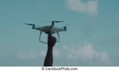 Male hand catching drone against sky - Male hand catching...