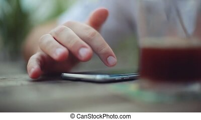 Male hand close up using smart phone app text messaging sms in summer outdoor cafe. 1920x1080