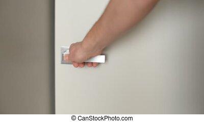 Male Hand Closing Door in Living Room.