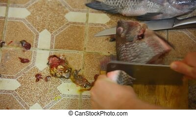 male hand cut fish into pieces and rinsed.