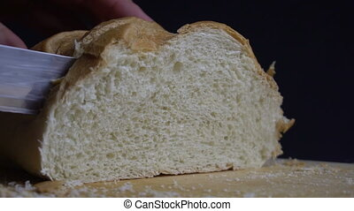 Male hand cutting loaf of bread. - Male hand cutting fresh...