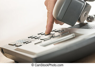Male hand dialing a classical landline telephone