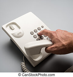 Male hand dialing telephone number using white landline...