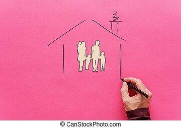 Male hand drawing a house shape around a paper cut family silhouette of five