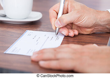 Filling Out The Amount On A Cheque - Male Hand Filling Out...