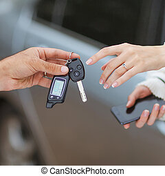 Male hand giving car key to female hand. She is holding a cell p