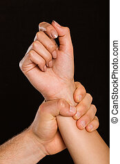 Male hand grabbing female wrist on black background