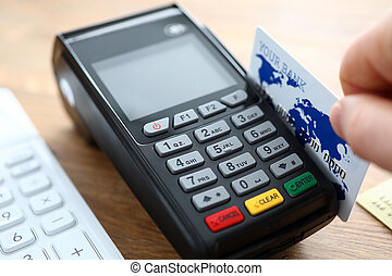 Male hand hold credit card with POS terminal closeup