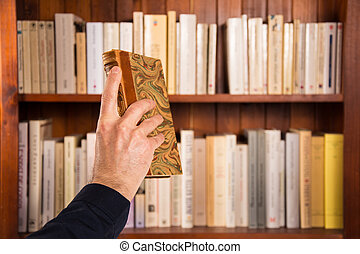 Male hand holding a book in front of bookshelves