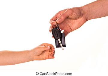Male hand holding a car key and handing it over to another person isolated