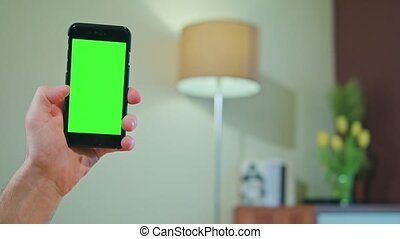 Male Hand Holding a Phone with a Green Screen