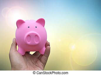 Male hand holding a pink piggy bank on blured background