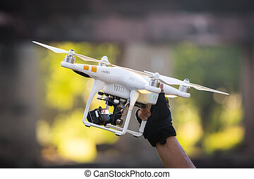 Male hand holding helicopter drone with checking battery.