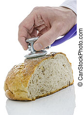 Male hand holding stethoscope on a loaf of bread