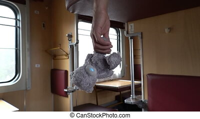 Male hand holding teddy bear, shaking while travelling by train