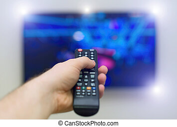 Male hand holding TV remote control.