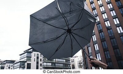 Male hand holding umbrella. The gust of wind pulls the...